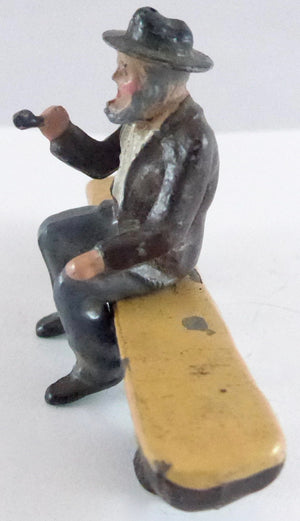 Britains aged villager with pipe on log seat, brown