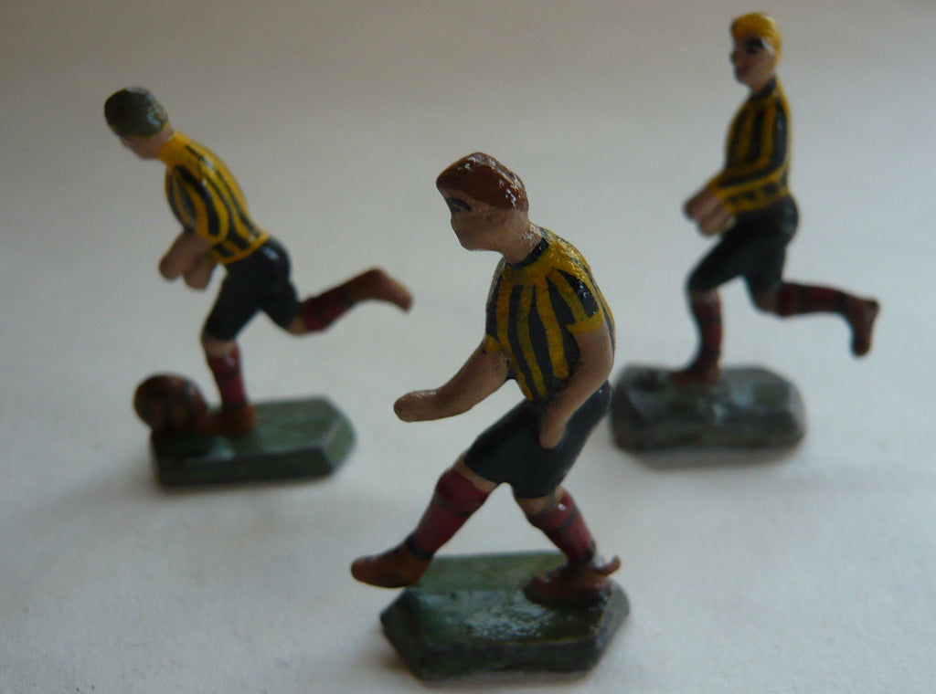 three small scale solid lead footballers in yellow/black strip