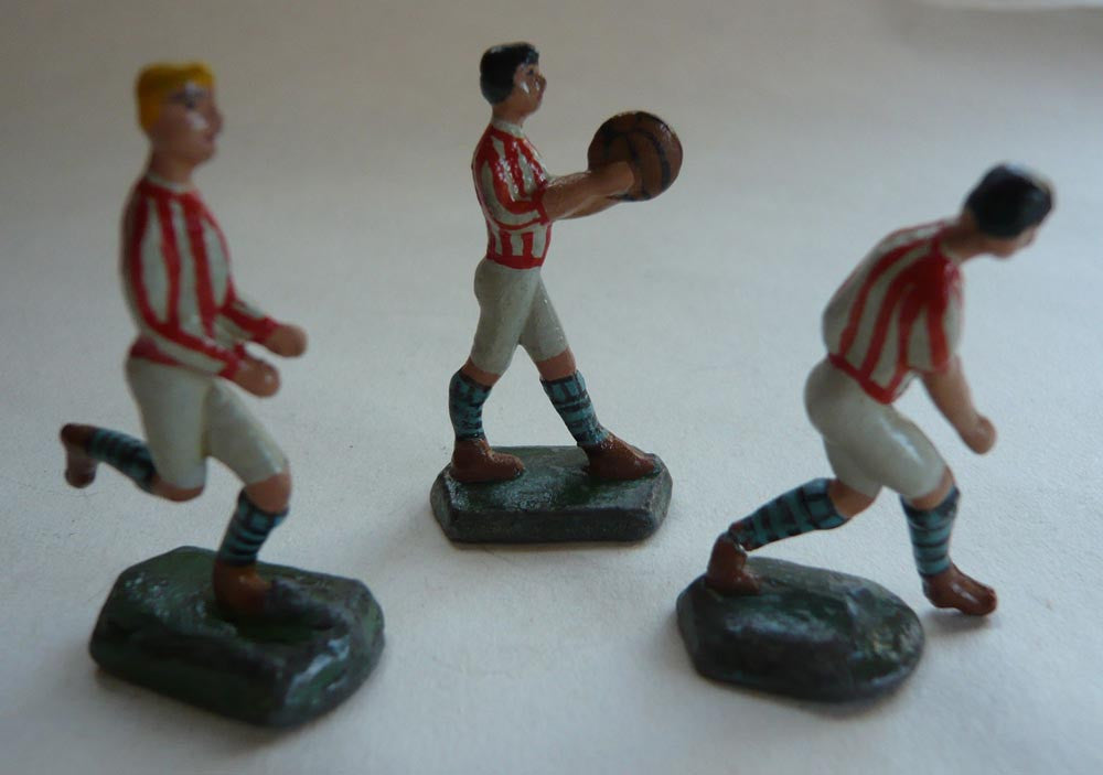 three small scale solid lead footballers in red/white strip