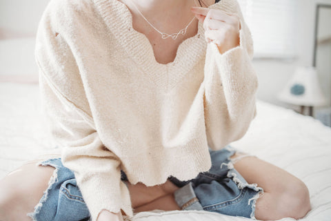 3 dainty sideways hearts necklace  on gal wearing cream sweater and casual jeans