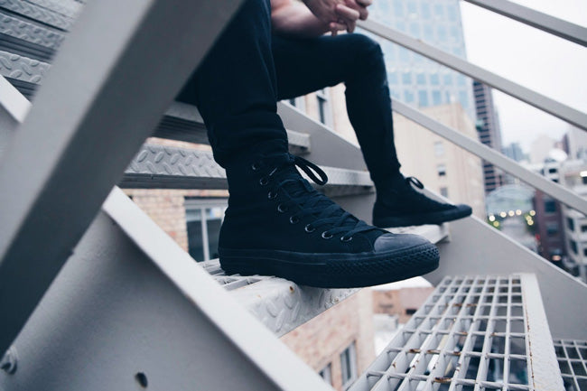 Close-up someone sitting on stairs wearing black pants and shoes