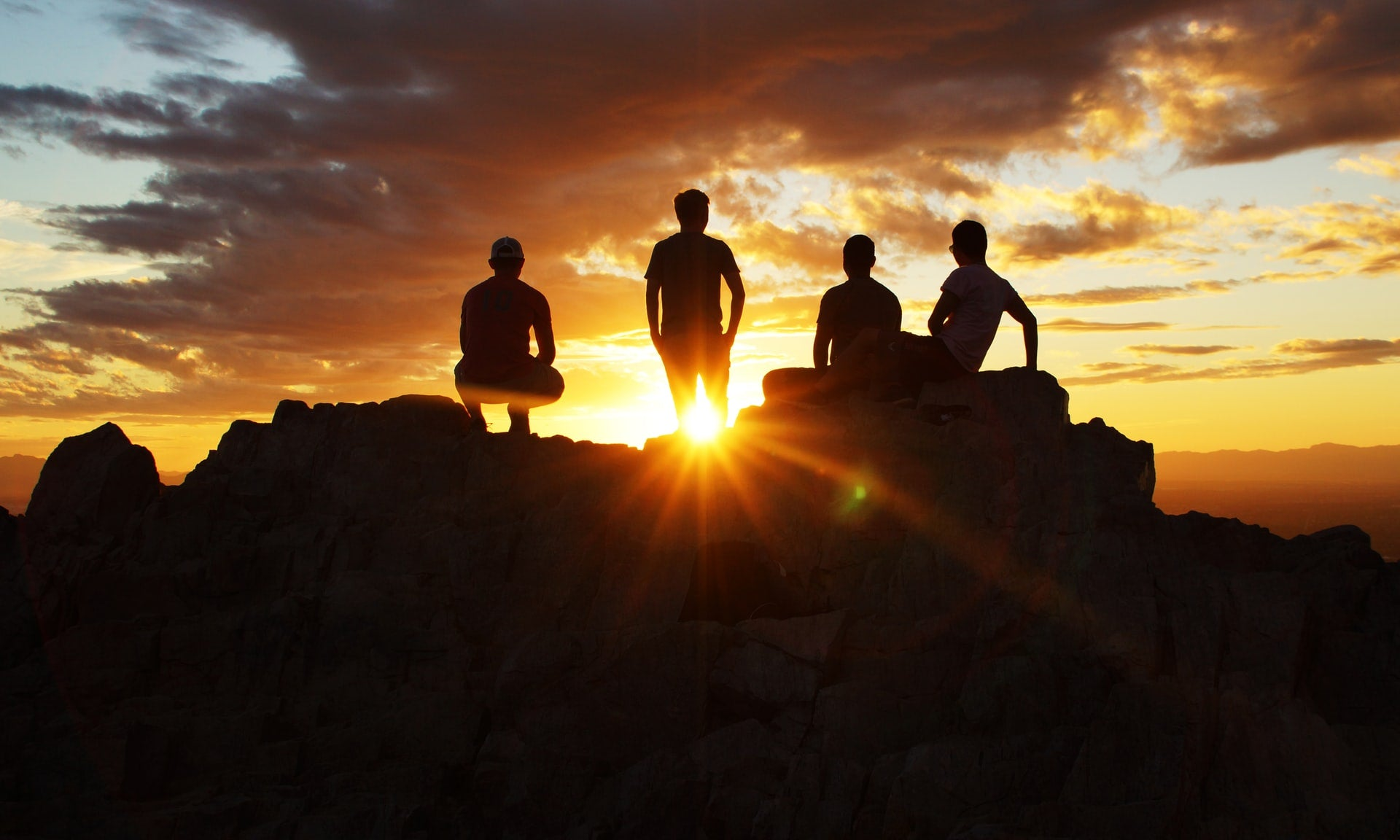 four friends enjoying a sunny view on top of a mountain