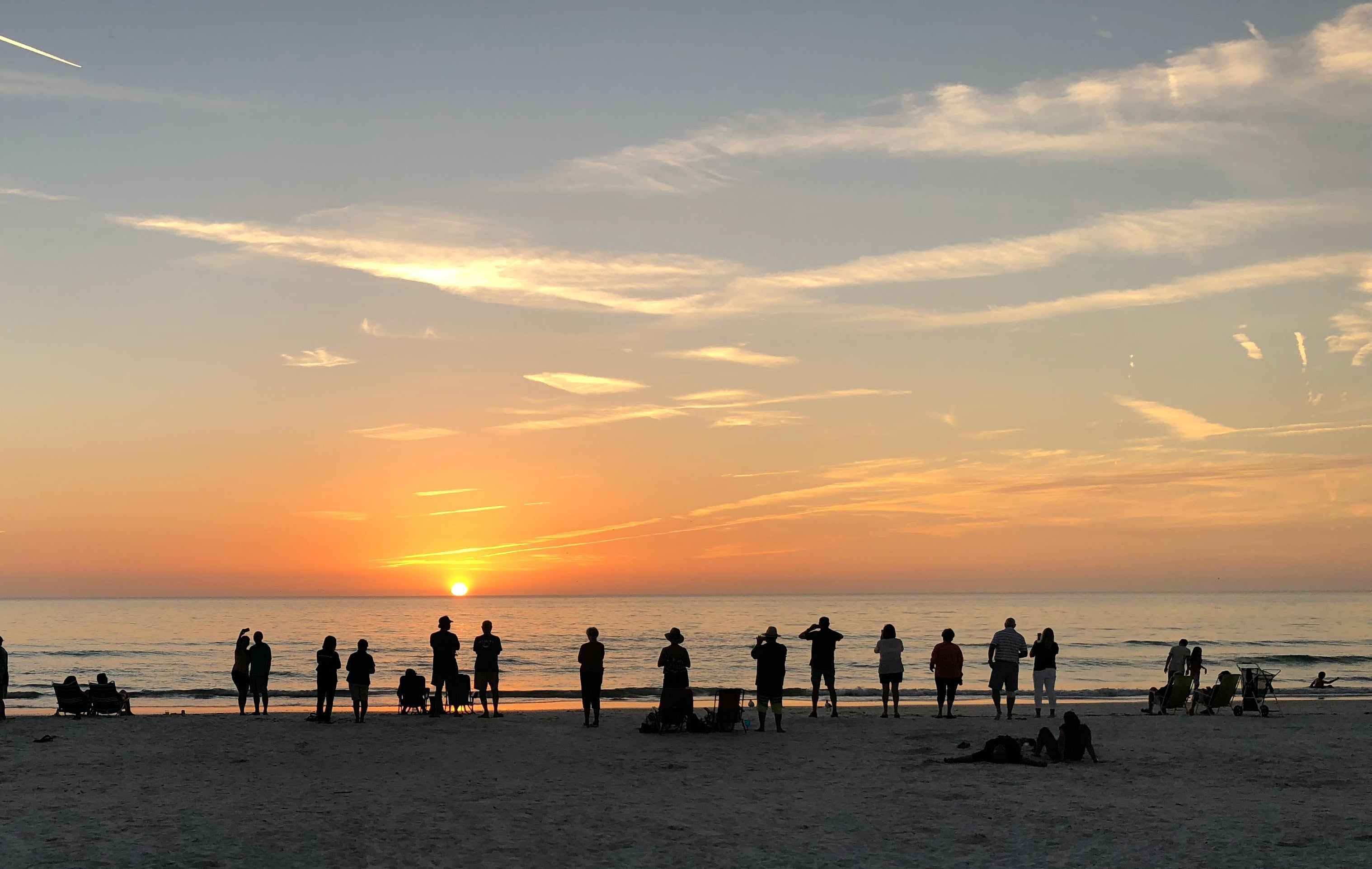 A group of friends enjoying the sunset at the beach