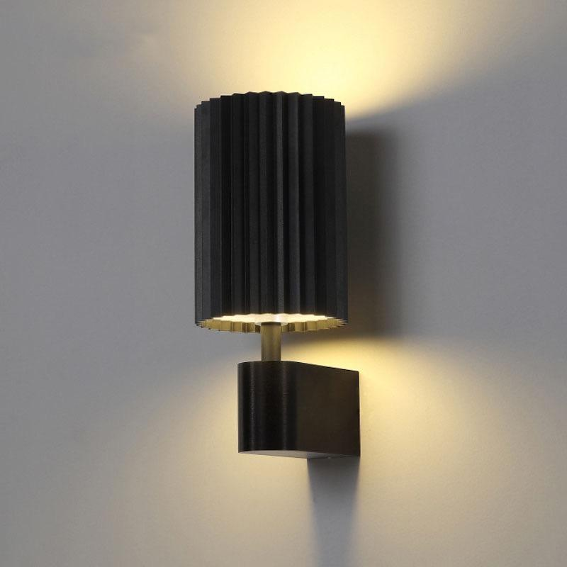 A black wall lamp with a pleated cylinder shape metal lampshade and black base.