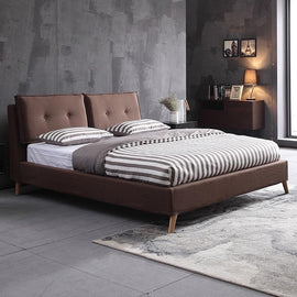 A dark brown fabric bed with two cushions, with two buttons each, on the headrest, light wooden lengs and striped brown and white bedding.