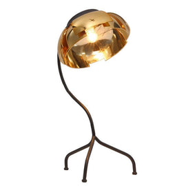 A lamp with a brass wire frame with three wire legs and copper coloured metal leaf shade that form the shape of a flower.