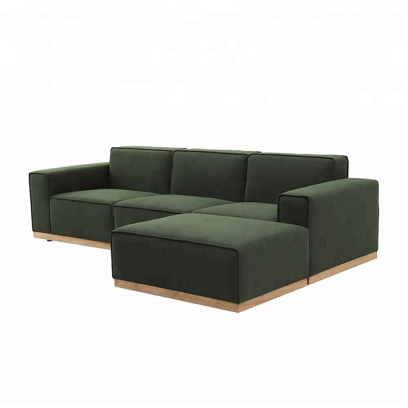 A Sectional Sofa consisting of a two seat and ottoman with an olive green fabric and neutral wooden base.