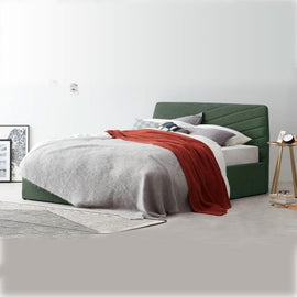 A green fabric bed with a broad base and no visible legs with long v-shaped pattern indents in the headboard.