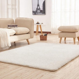 A large beige living room rug, in front of a pale living room sofa set on a wooden floor.