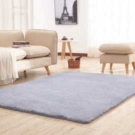 A large grey living room rug, in front of a pale living room sofa set on a wooden floor.