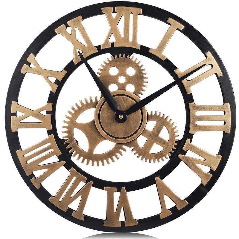 A wall clock with a black border and metal roman numeral clockface as well as three metal gears at the center and black clockhands.