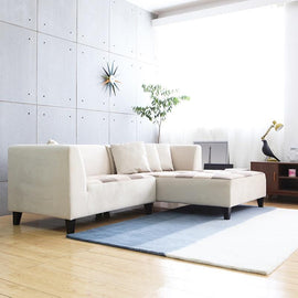 A Sectional sofa with a neutral beige fabric, patchwork seat, short black wooden legs and beige scatter cushions.