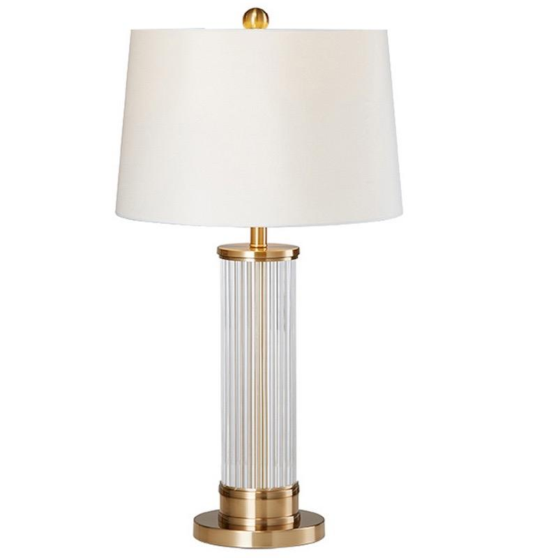 A table lamp with a gloss transparent column-shaped body, gold finishings and base and a pearl white lampshade.