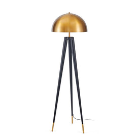 A tripod shaped floor lamp with thin black legs that end with a golden finish at the base and a dome shaped golden metal lamp-shade.