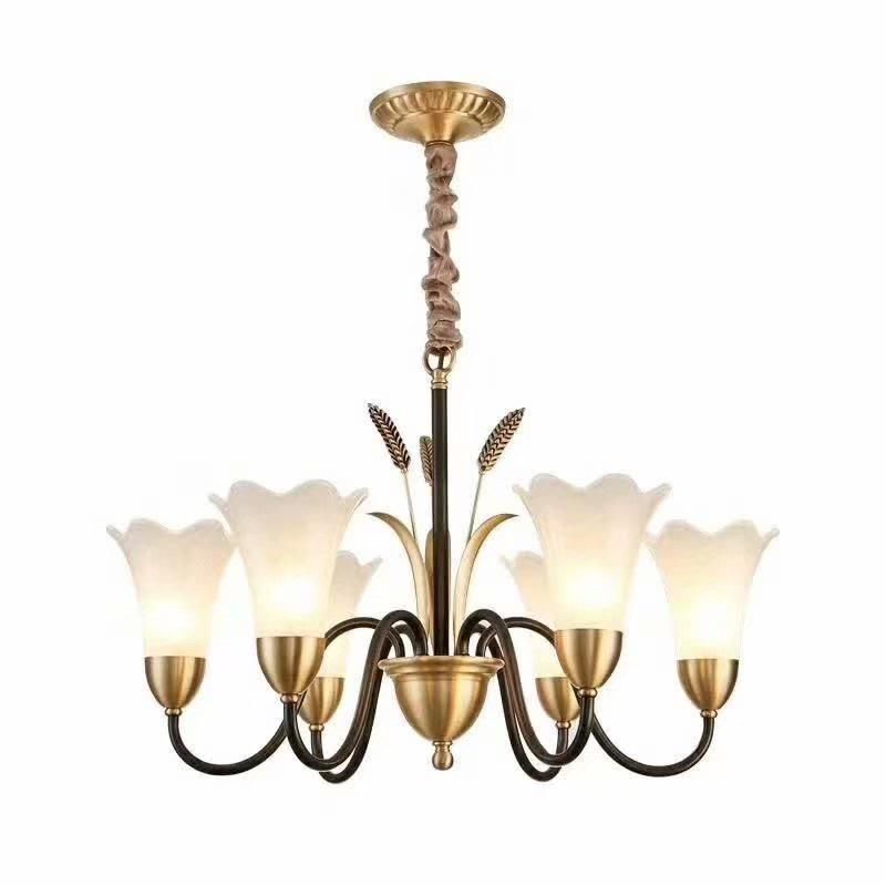 A chandelier with a brass and golden frame and three leaves with golden wheat stalks in the center that has six upward curving arms containing glass lily-shaped shades in a golden base.