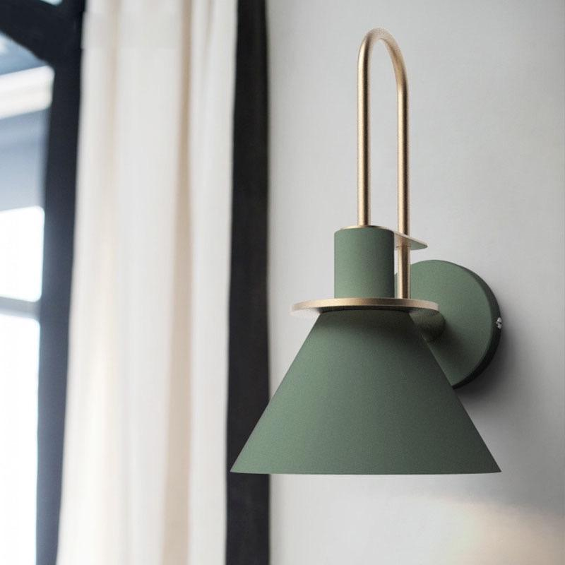 A cone-shaped olive green wall light with a golden metal fitting.