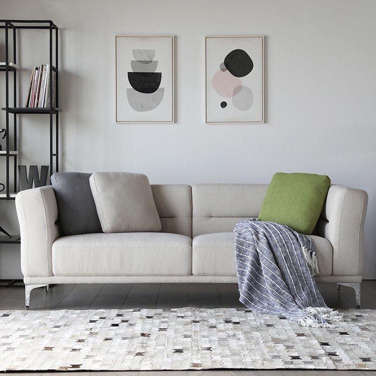 A grey, three-seat sofa with metal legs and a line pattern in backrest with three scatter cushions in green, blue and grey.