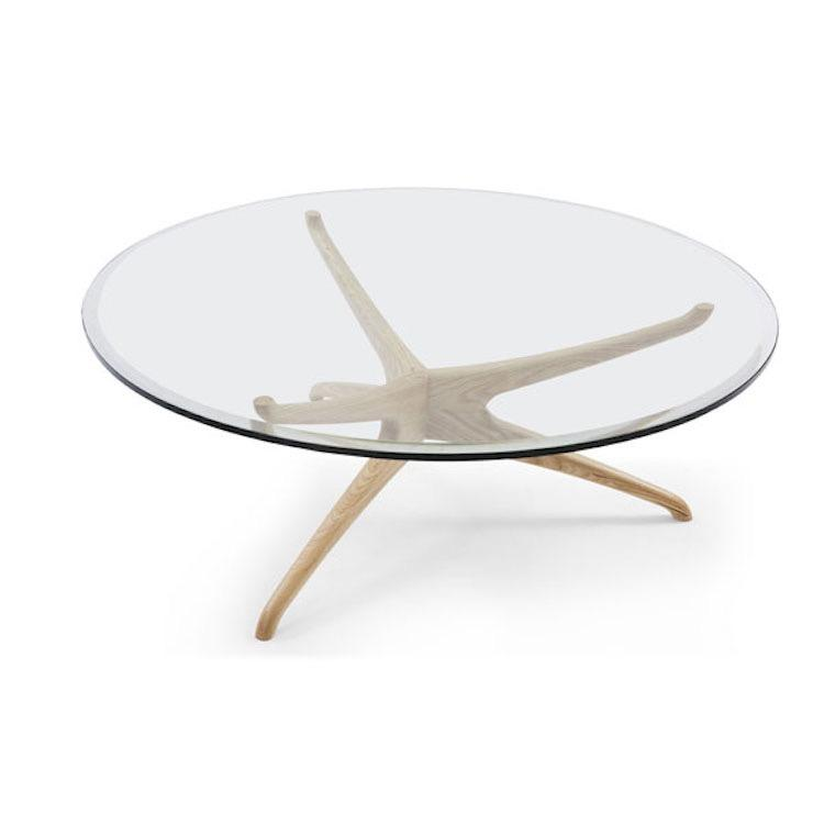 A round coffee table with three wooden legs that support a round glass top.