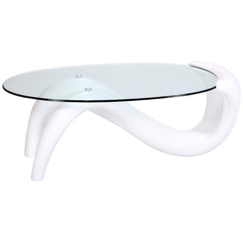 A coffee table that has a two-pronged glossy white, wave shaped base that connects to a side of the oval glass top.