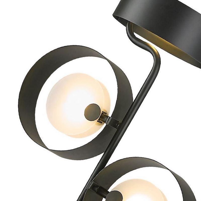 A floor lamp with three black, metal lamp shades containing orbs, on the top-left, top-right and top of the structure.