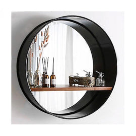 A wall mirror with a wide, black metal rim and a wooden shelf attached in the middle containing decor items.