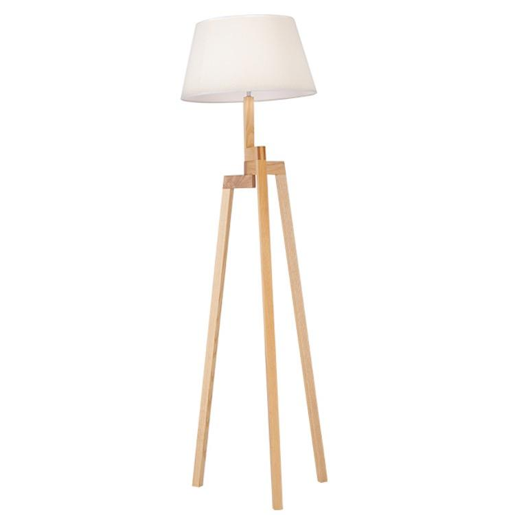 A floor lamp with three wooden legs connected at different heights, at a right angle to the white lamp shade.
