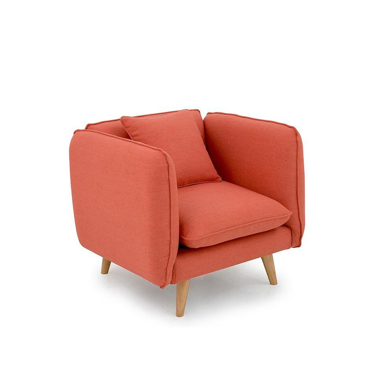 A tuxedo-style light red armchair with padded body and pine-coloured medium wooden legs.