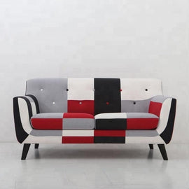 A patchwork style, grey, white, black and red two-seat sofa with black legs.