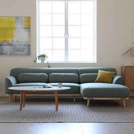 Green sectional sofa consisting of a two seat sofa and couch, with a light pine wood base.