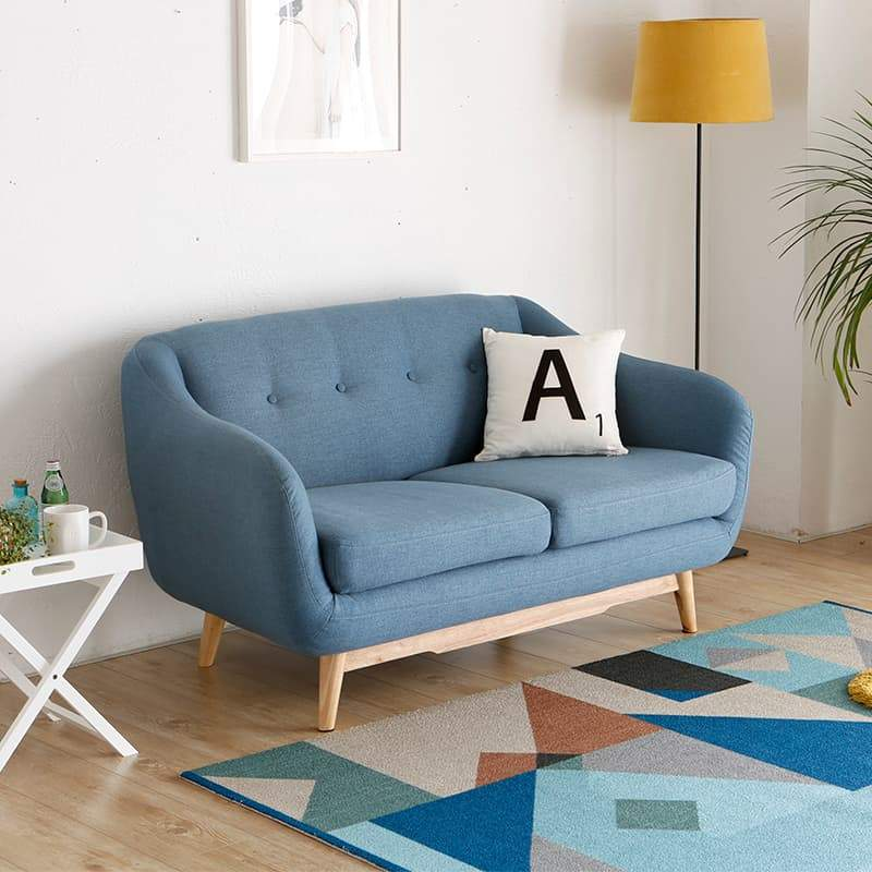 A Mid-Century modern three-seat sofa with blue fabric, a pine coloured wood base and buttons in the backrest.