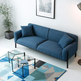 A denim blue fabric sofa with two scatter cushions and a black metal base structure with five short legs.