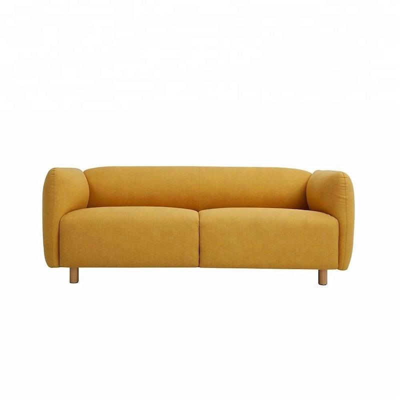A lawson style two-seat sofa with bright yellow fabric and short wooden legs.