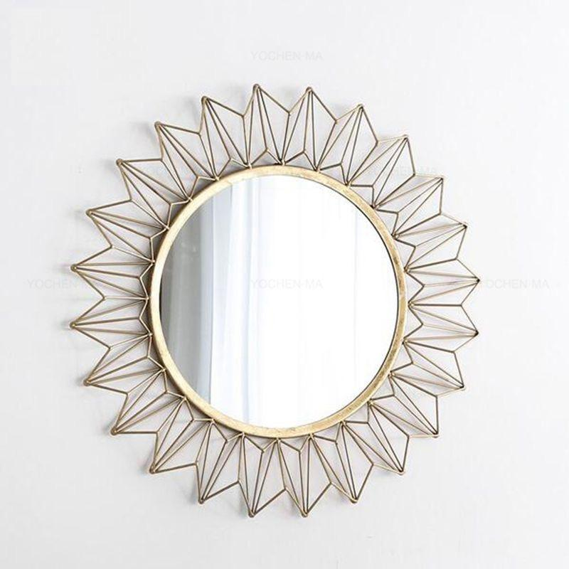 A round mirror with a gold frame and fractal triangle shapes surrounding it.