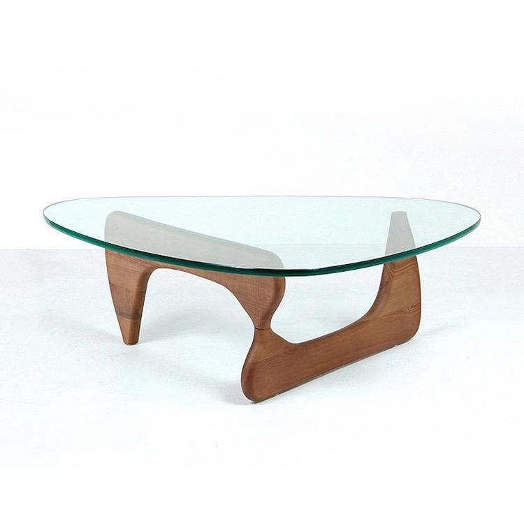 A triangle shaped coffee table with a curved, triangular wooden base and a triangle glass top.