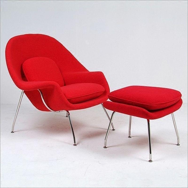 A sleek modern, red low armchair with a silver metal frame and a red ottoman with silver metal legs.