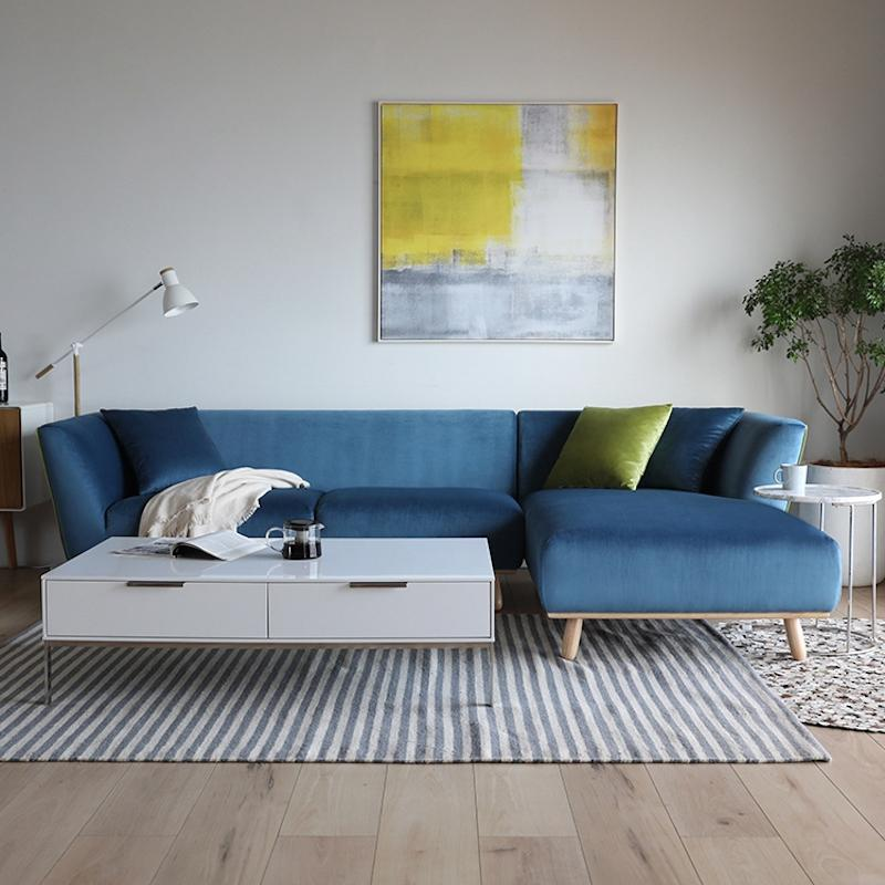 A two-seat and couch sectional sofa in a soft blue fabric with a neutral, natural wooden base.