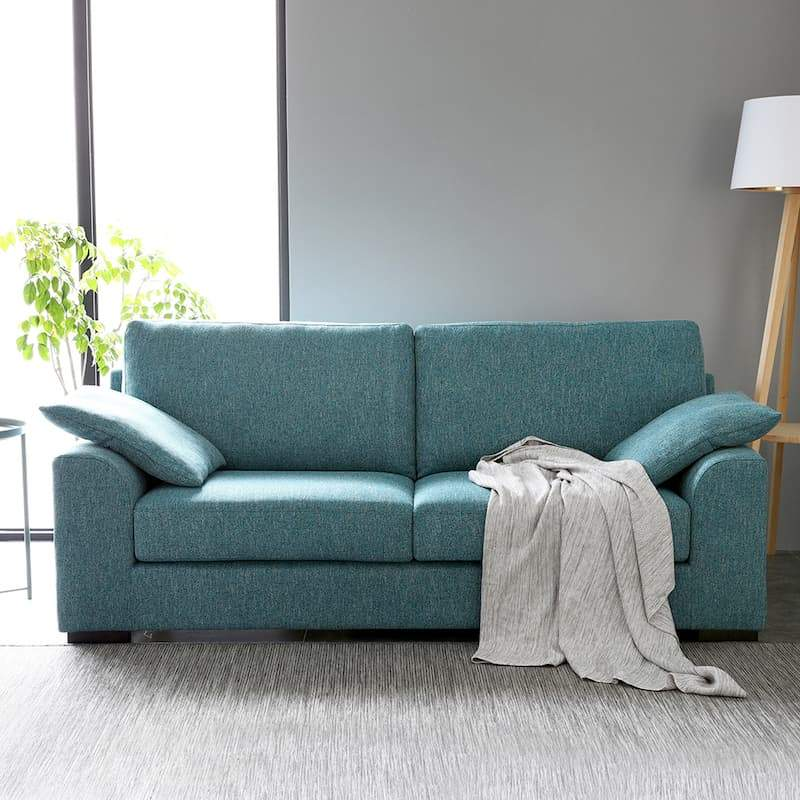 A lawson style blue sofa with a scattercushion on each armrest and short, square black legs.