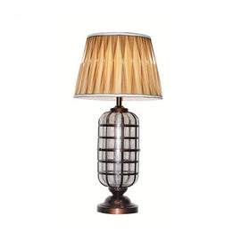 A brass-colour lamp with a lantern shaped body and gold pleated lampshade.