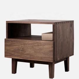 A solid walnut bedside table with one drawer and one open-back shelf above.