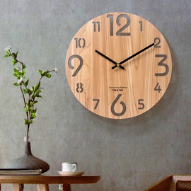 A wooden wall clock with a wood grain texture and cut-out numbers and black clock hands.