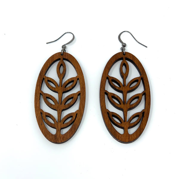 Close up of all wooden earrings with the shape of wild rice in an oval.