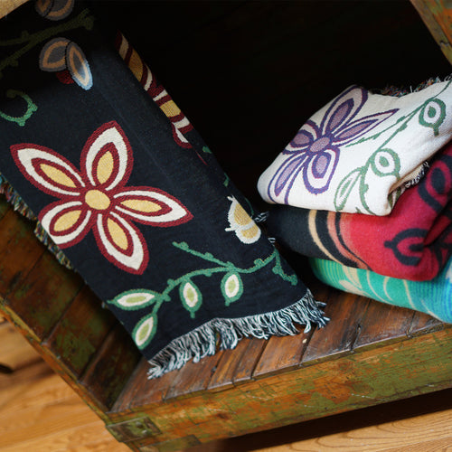 Blankets folded and on display in a wooden cabinet.