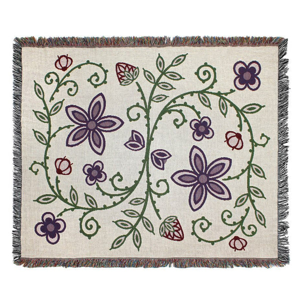 Product photo oof Woodlands throw blanket in light/cream color, design shows- strawberries, wild rice, blueberries, and a green vine connecting all the plants
