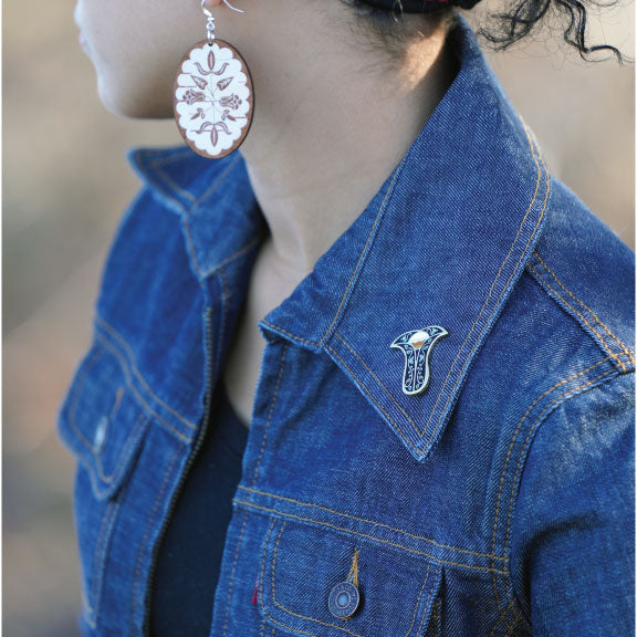 Person in jean jacket with Next Generation pin on left collar and Birch Bloom earrings