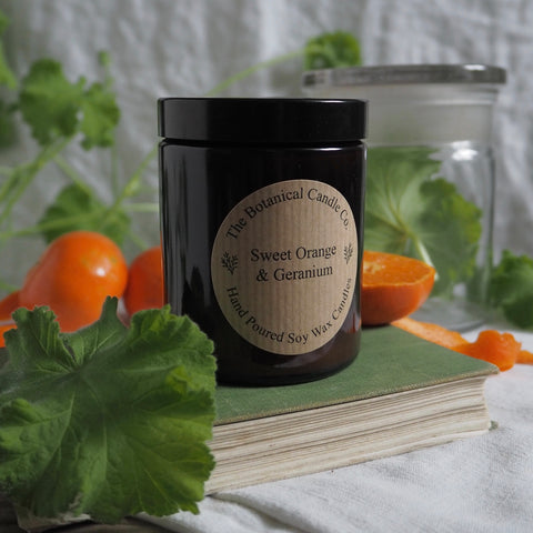 THE BOTANICAL CANDLE CO. MEDIUM 180ML AMBER GLASS JAR CANDLE - SWEET ORANGE AND GERANIUM