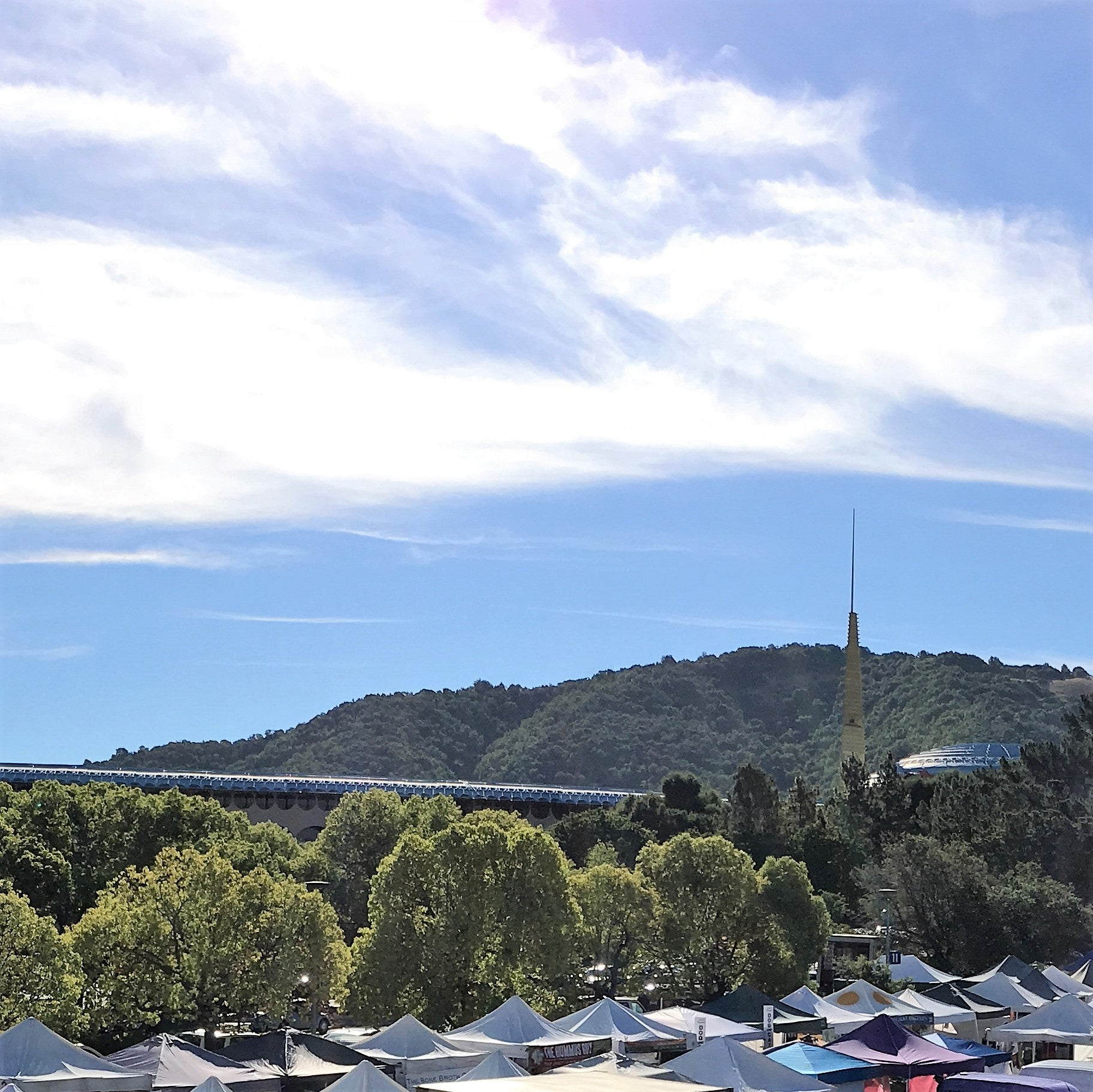 San Rafael Civic Center Spire and Hills under a Blue sky with whispy clouds and mostly white Market tent tops in the foreground