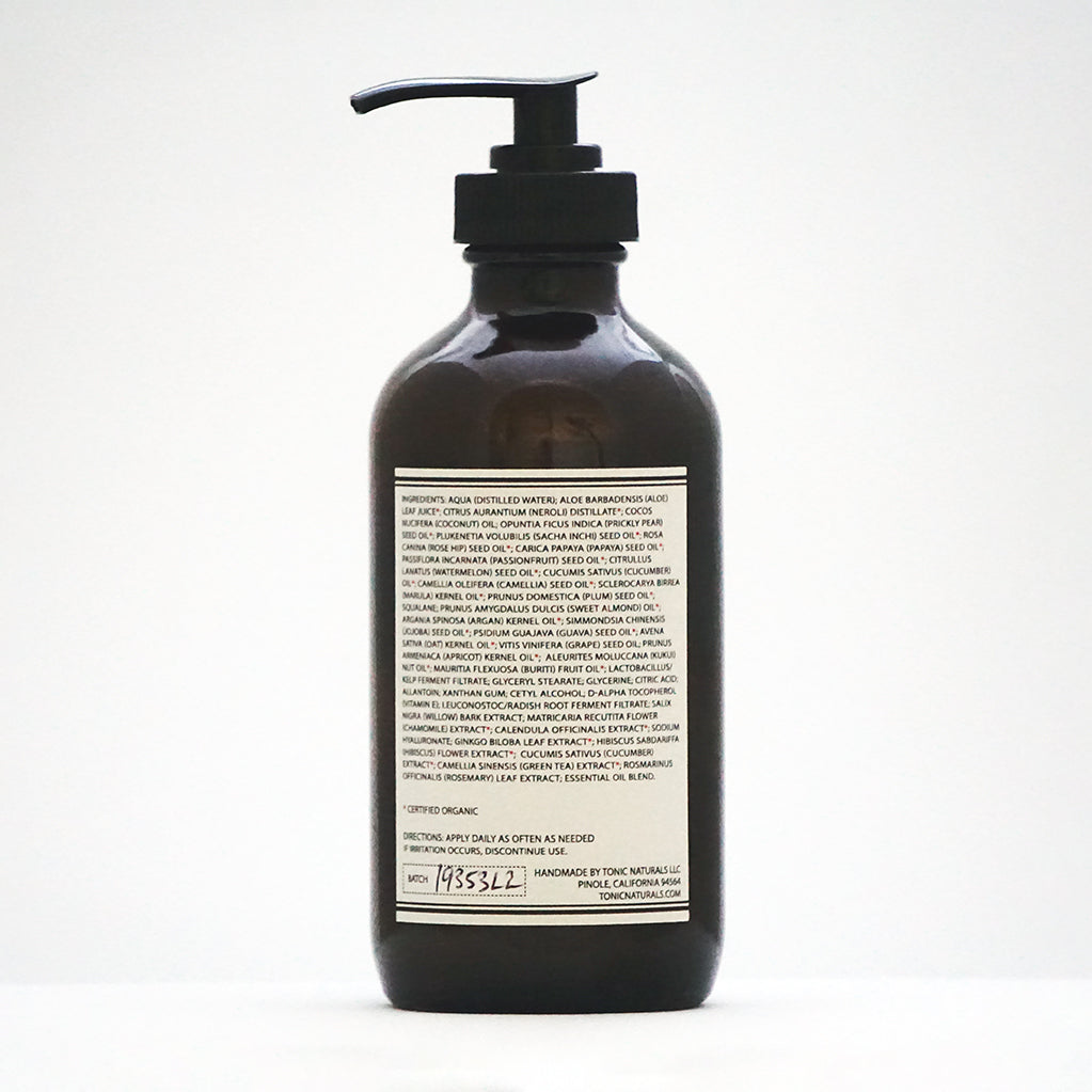 Front view of TONIC Neroli Body Lotion in an amber glass bottle with black pump