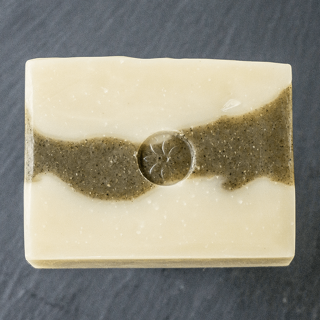 an unwrapped bar of Tonic Naturals Spruce and Fir soap on a black slate background