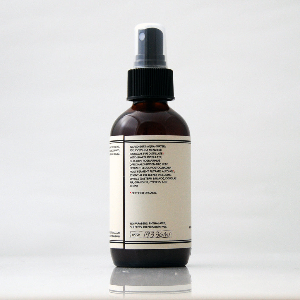 Spruce and Fir Aromatic Essential Oil Room Mist in an amber glass bottle with black pump on an off white background