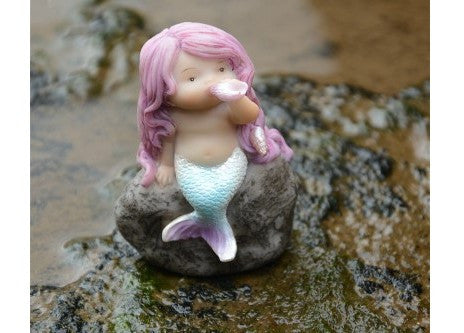 Little Mermaid playing with shell